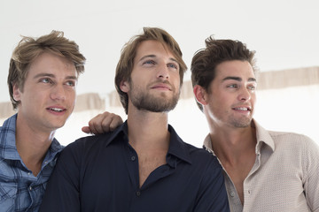Three male friends looking away