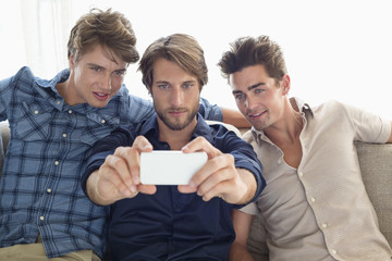 Man sitting with friends taking picture with mobile phone