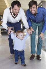 Parents helping their son to walk