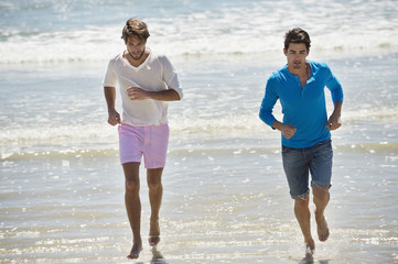 Two male friends running on the beach