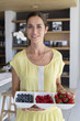 Portrait of a woman holding a tray of assorted berries at home