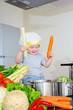 Happy child at kitchen preparing soup