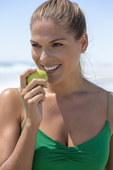 Smiling woman eating a green apple