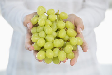 Close-up of a woman's hand holding bunch of grapes