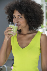 Portrait of a woman drinking kiwi shake
