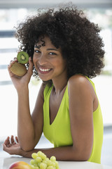 Portrait of a smiling woman showing kiwi fruits
