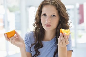 Portrait of a woman holding an orange