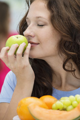 Close-up of a woman smelling a green apple