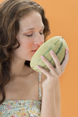 Close-up of a woman smelling melon