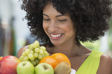 Smiling woman holding a plate of fruits
