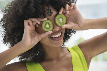 Woman holding kiwi fruits in front of her eyes