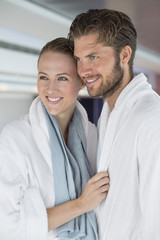 Close-up of a smiling couple in bathrobes at spa