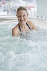 Portrait of a smiling woman in a hot tub