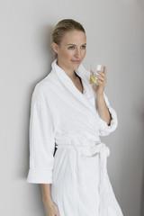Woman in bathrobe drinking lemonade at spa