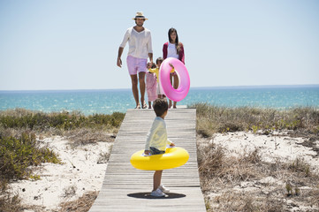 Children with their parents holding inflatable rings on a boardwalk on the beach