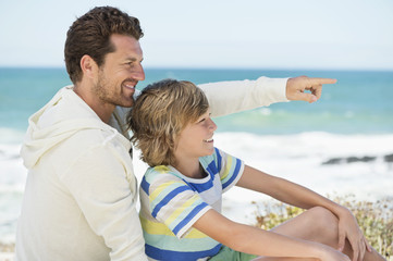 Man pointing with his son on the beach