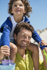 Man carrying his son on shoulders on the beach