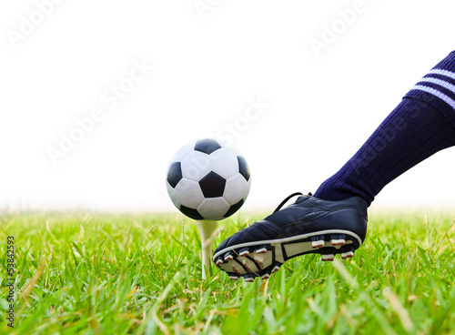 foot kicking soccer ball on golf tee isolated