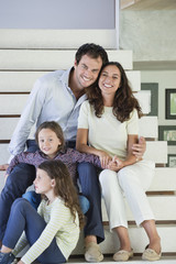 Couple with their children sitting on steps