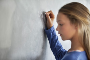 Close-up of a girl writing on a blackboard in a classroom