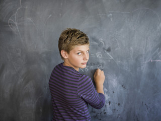 Boy writing on a blackboard in a classroom