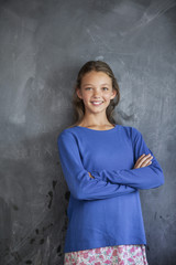 Girl smiling with his arms crossed in front of a blackboard in a classroom