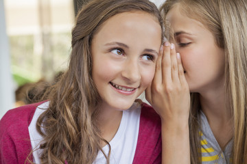 Close-up of two girls whispering in a school