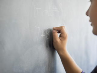 Close-up of a boy writing on a blackboard in a classroom