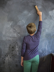 Boy cleaning blackboard with a duster in a classroom