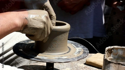 Potter's hands working clay on potter's wheel