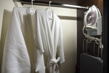 Close up of clothes hanger and twins bathrobe in wooden wardrobe