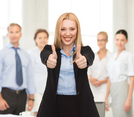 businesswoman with thumbs up in office