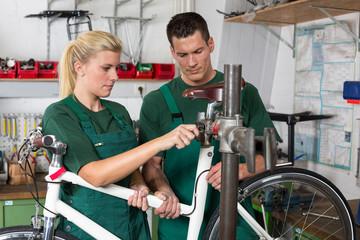 Bicycle mechanic and apprentice repairing a bike