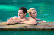 Happy smiling couple in swimming pool