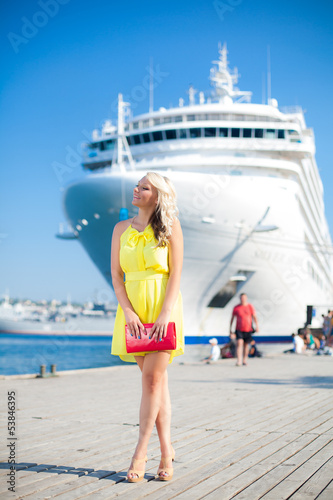 Beautiful Woman in a dock, big cruise ship on background