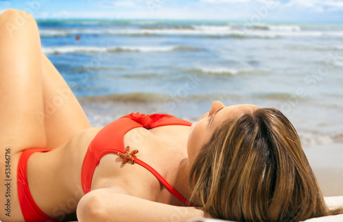 Woman in bikini relaxing on the beach