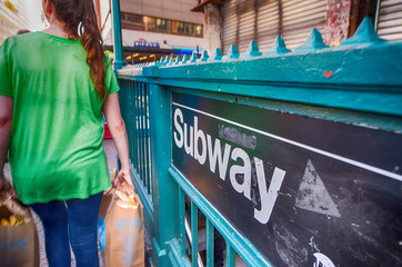 Girl passing in front of a Subway entrance in New York City