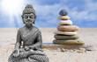 Steinpyramide mit Buddha auf Sand und Holz