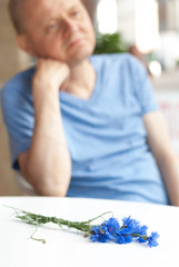 Man waiting at table with bunch of blue cornflowers