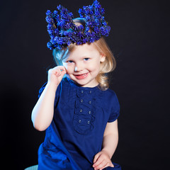 Little cute girl posing in crown of blue flowers
