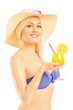 Beautiful blond female in bikini holding a cocktail