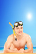 Young man wearing a snorkeling mask on a beach