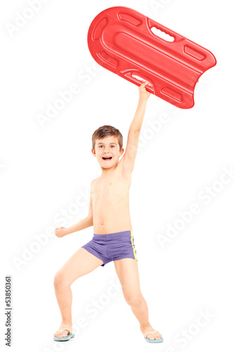 Full length portrait of a boy holding a swimming float and gestu