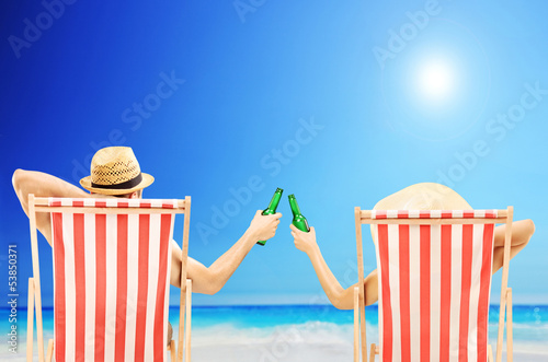 Man and woman relaxing on a beach and cheering with beers