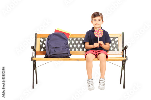 School boy sitting on a bench and holding a candy lollipop