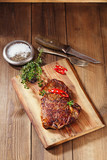 beef steak with red chillies on wood and table