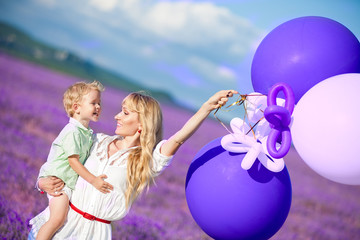 Mother and son playing with balloons on beautiful summer day