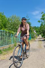 Woman riding a bicycle down a rural lane
