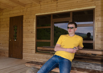 Man sitting in front of a wooden cabin
