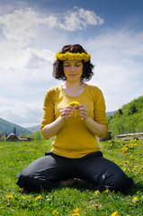 Young woman sitting in a meadow